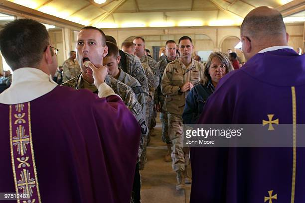 Catholics partake in Communion at a Catholic Mass on March 7 2010 in Kandahar Air Field in southern Afghanistan Military chaplains hold services on...