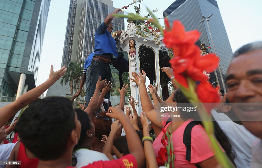 Catholics reach for flowers during a procession marking the day of Saint Sebastian, the patron saint of Rio, on January 20, 2015 in Rio de Janeiro, Brazil. Brazil is home to more Catholics than any other country in the world.