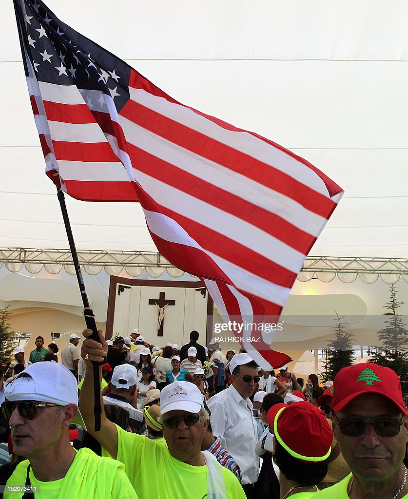 US Catholics wave the American flag at the end of a mass led by Pope Benedict XVI at Beirut's waterfront on September 16, 2012. Pope Benedict XVI prayed that Middle East leaders work toward peace and reconciliation, stressing again the central theme of his visit to Lebanon, whose neighbour Syria is engulfed in a civil war. AFP PHOTO / PATRICK BAZ