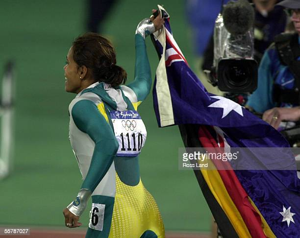 Cathy Freeman sets off on a lap of honour carrying the Australian and Aboriginal flags the Olympic Stadium Sydney Monday after her win in the Women's...