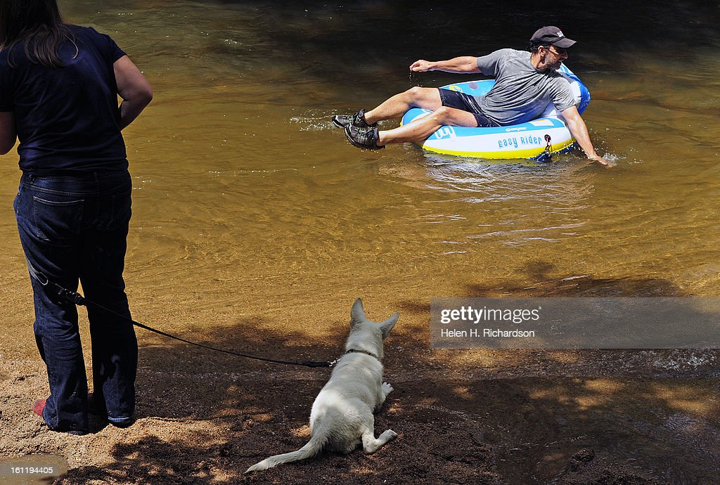 Cathy Lopez-Wessell, left, brought her new 12 week old white german shepherd Bodhi to enjoy the cool waters of the creek. The puppy seemed more interested in the people floating by on their inner tubes. To escape the rising temperatures folks hit the water along Boulder creek to cool off today July 18th, 2012. Helen H. Richardson, The Denver Post