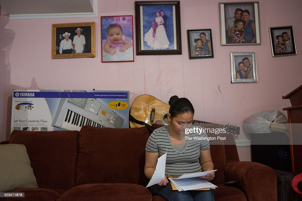 Catia Paz who graduated from high school in Woodbridge VA and now works two jobs in the area looks over her legal documents at the family home in...