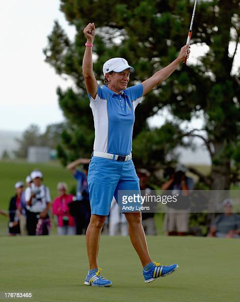 Catriona Matthew of Scotland and the European Solheim Cup team celebrates after making a putt to win the Solheim Cup during the final day singles...