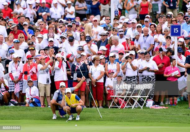 Catriona Matthew of Team Europe lines up her putt with caddie Mike Patterson on the 15th green during the morning foursomes matches of the Solheim...