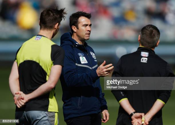 Cats head coach Chris Scott speaks to the umpires before warm up during the round 21 AFL match between the Geelong Cats and the Richmond Tigers at...