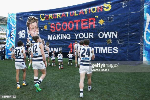 Cats players walk to their banner during the round 22 AFL match between the Collingwood Magpies and the Geelong Cats at Melbourne Cricket Ground on...