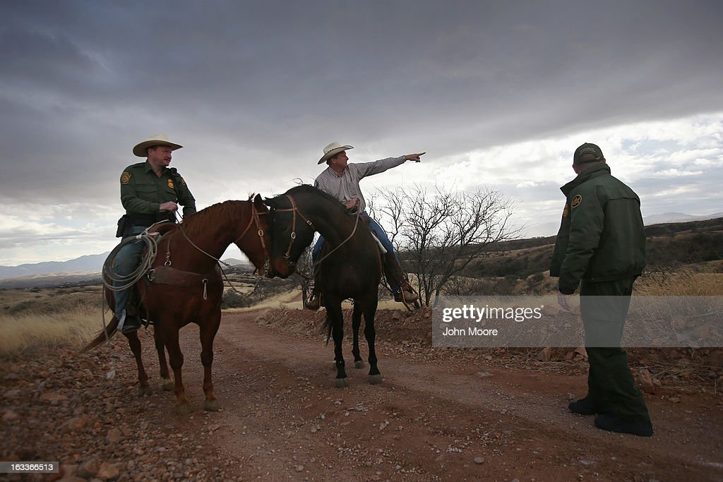 Cattle rancher Dan Bell (C) points toward a group of people walking along the Mexican side of the U.S.-Mexico border fence on March 8, 2013 in Nogales, Arizona. The third generation Arizona rancher, who grazes cattle on ten miles of land along the U.S. border with Mexico, was meeting with U.S. Border Patrol ranch liaison agent John 'Cody' Jackson (L). The Border Patrol's ranch liaison program in Nogales is designed to help coordinate with ranchers, who live on the front lines of border security conflicts, including drug smuggling and immigrants crossing in from Mexico.