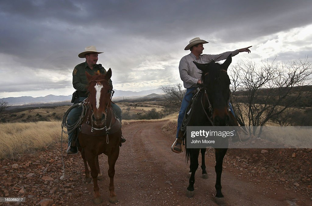 Cattle rancher Dan Bell (R) points toward a group of people walking along the Mexican side of the U.S.-Mexico border fence on March 8, 2013 in Nogales, Arizona. The third generation Arizona rancher, who grazes cattle on ten miles of land along the U.S. border with Mexico, was meeting with U.S. Border Patrol ranch liaison agent John 'Cody' Jackson (L) on Bell's ZZ Cattle Ranch. The Border Patrol's ranch liaison program in Nogales is designed to help coordinate with ranchers, who live on the front lines of border security conflicts, including drug smuggling and immigrants crossing in from Mexico.