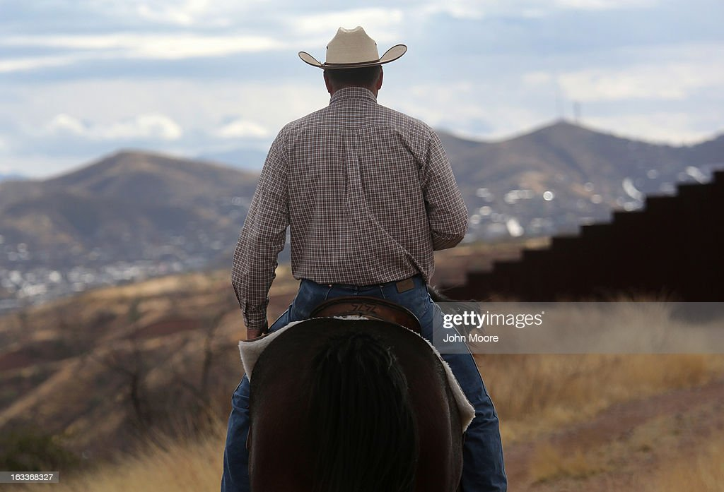 Cattle rancher Dan Bell rides through his ZZ Cattle Ranch at the U.S.-Mexico border fence on March 8, 2013 in Nogales, Arizona. Bell, a third generation Arizona rancher, grazes cattle on nearly ten miles of border property and meets regularly with U.S. Border patrol agents to discuss border issues such as drug smuggling and illegal immigration.
