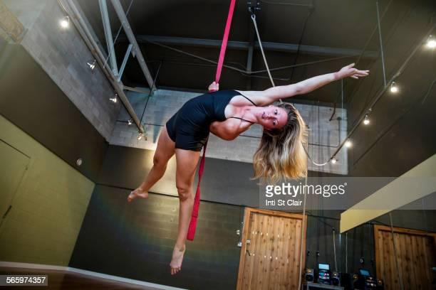 Caucasian acrobat hanging from ropes in studio