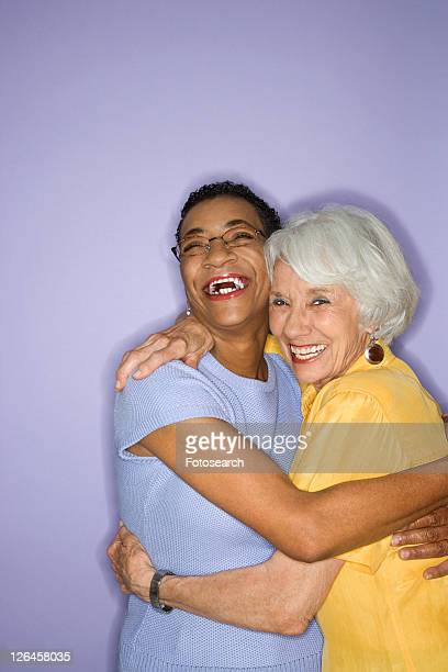 Caucasian and African American mature adult female embracing.