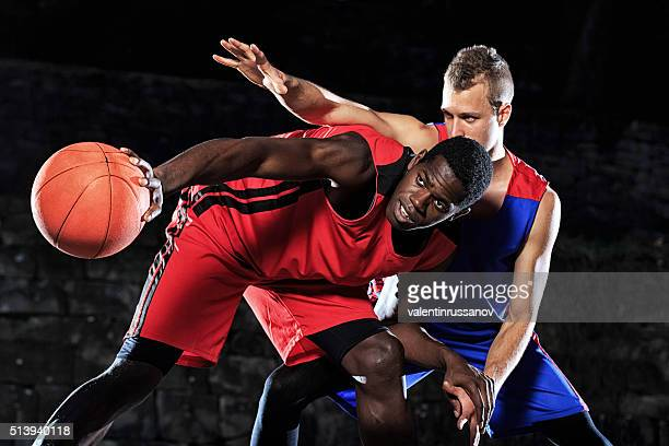 Caucasian and african basketball players in defence on black background