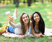 Caucasian and Asian young woman doing selfie and showing tongues. Funny girl friends having fun in free time in sunny park. International women friendship. Beautiful female models on picnic