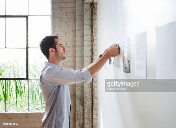Caucasian architect hanging photos in office
