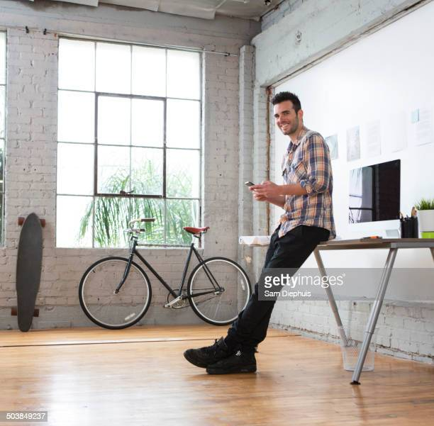 Caucasian architect using cell phone in office