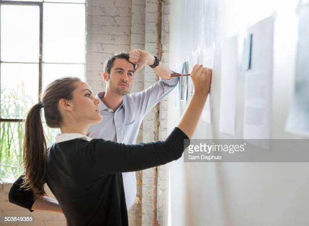 Caucasian architects drawing on photos in office