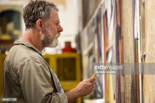 Caucasian artist drawing in studio