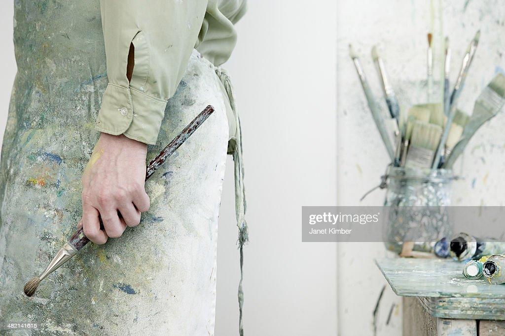 Caucasian artist holding paintbrush in studio