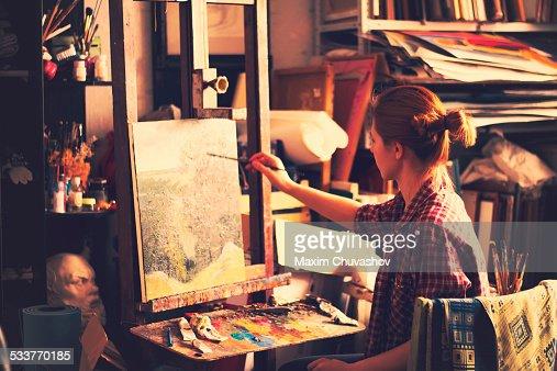 Caucasian artist painting on canvas in studio