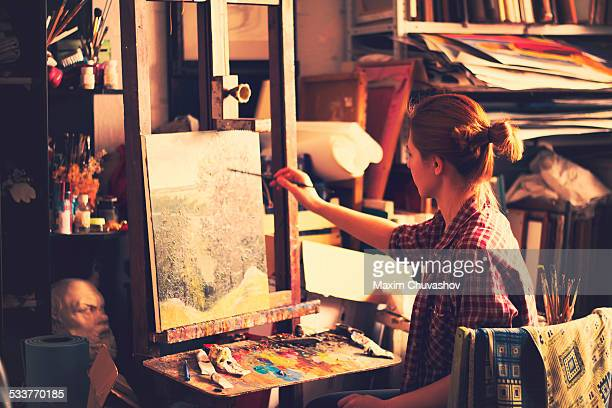 Caucasian artist painting on canvas in studio