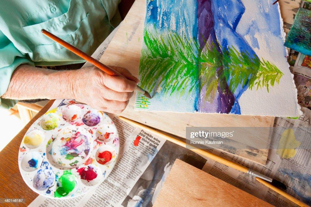 Caucasian artist painting watercolor tree