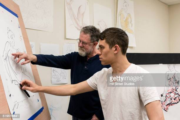Caucasian artist teaching student in studio