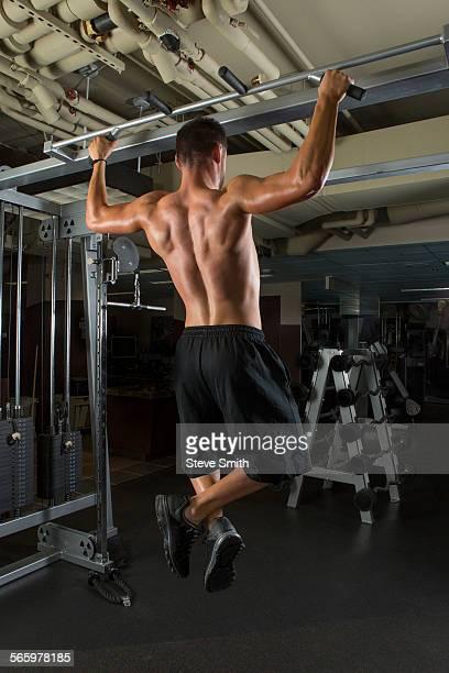 Caucasian athlete doing pull-ups in gymnasium