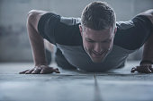 Caucasian athlete doing push-ups on floor