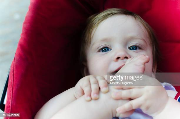 Caucasian baby boy chewing his toes