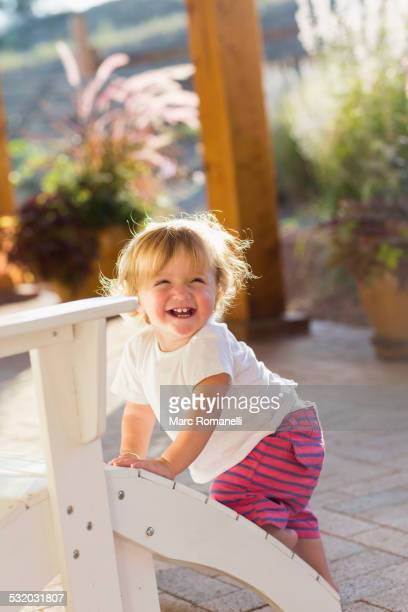 Caucasian baby boy climbing adirondack chair on patio