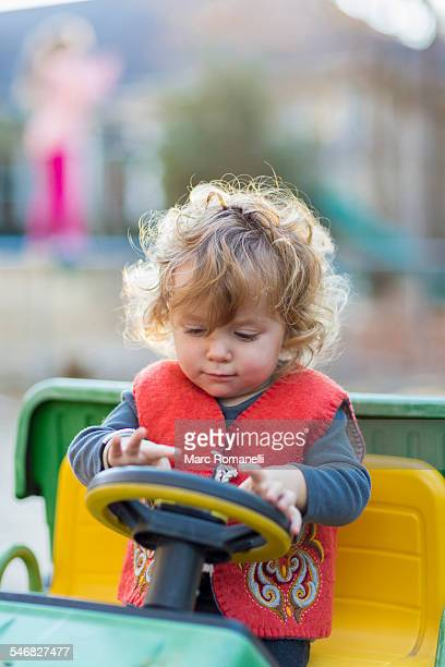 Caucasian baby boy driving toy tractor