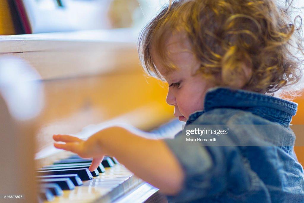 Caucasian baby boy playing piano