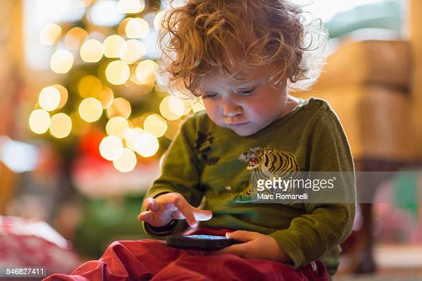 Caucasian baby boy playing with cell phone