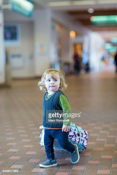 Caucasian baby boy rolling luggage in airport
