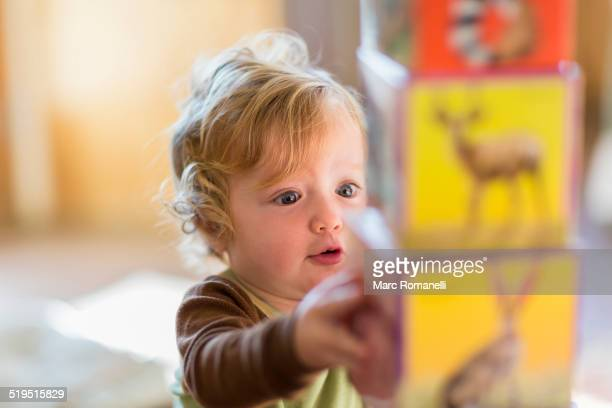 Caucasian baby boy stacking colorful blocks