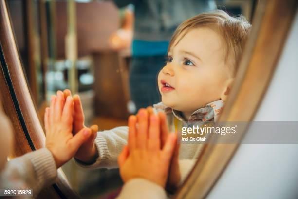 Caucasian baby boy standing at mirror