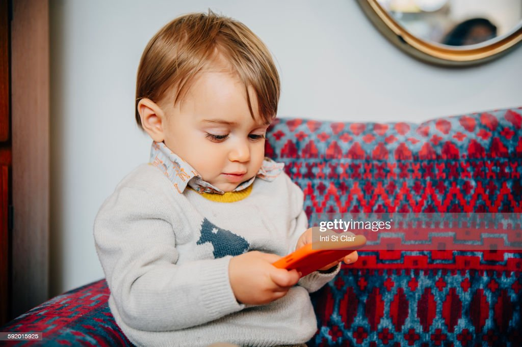Caucasian baby boy using cell phone on sofa