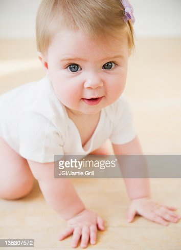 Caucasian baby crawling on floor : Stock Photo