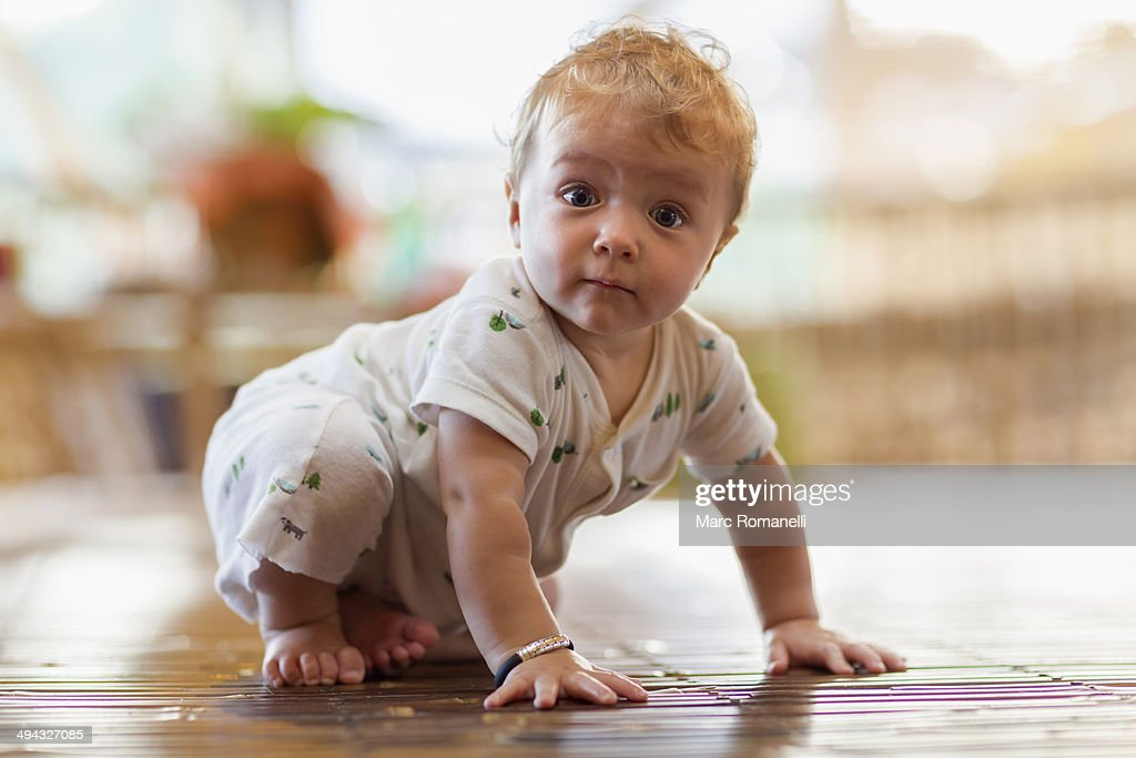 Caucasian baby crawling on floor