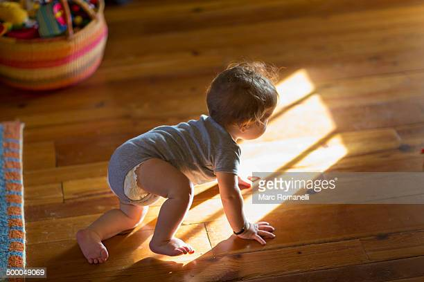 Caucasian baby crawling on floor
