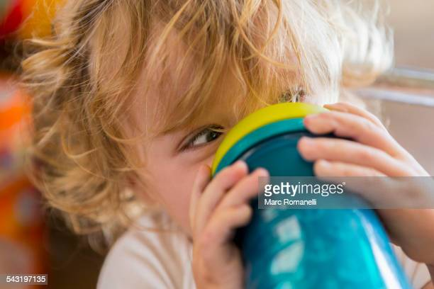 Caucasian baby drinking water from cup