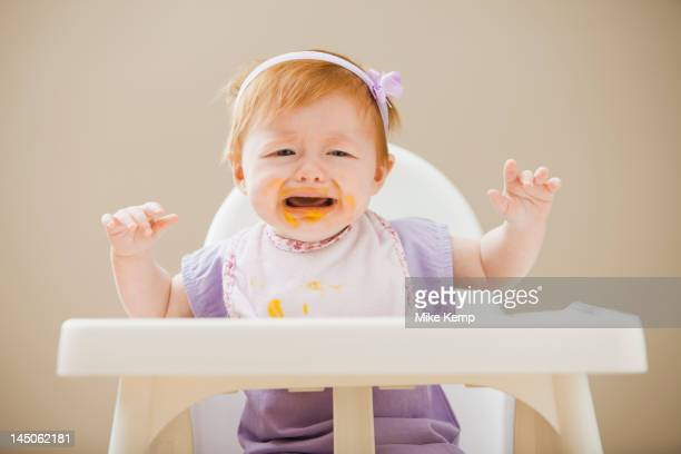 Caucasian baby girl crying in high chair