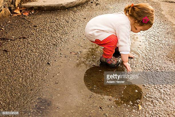Caucasian baby girl playing in puddle