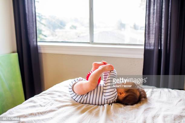 Caucasian baby girl playing on bed