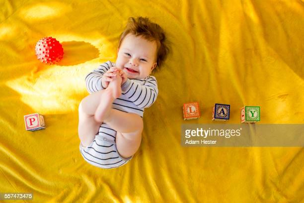 Caucasian baby girl playing with blocks on bed