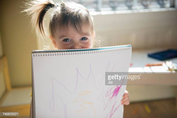 Caucasian baby girl showing drawing on sketchpad