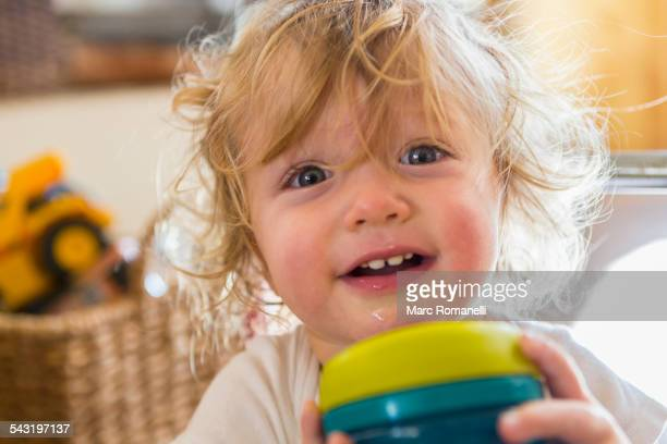 Caucasian baby holding cup