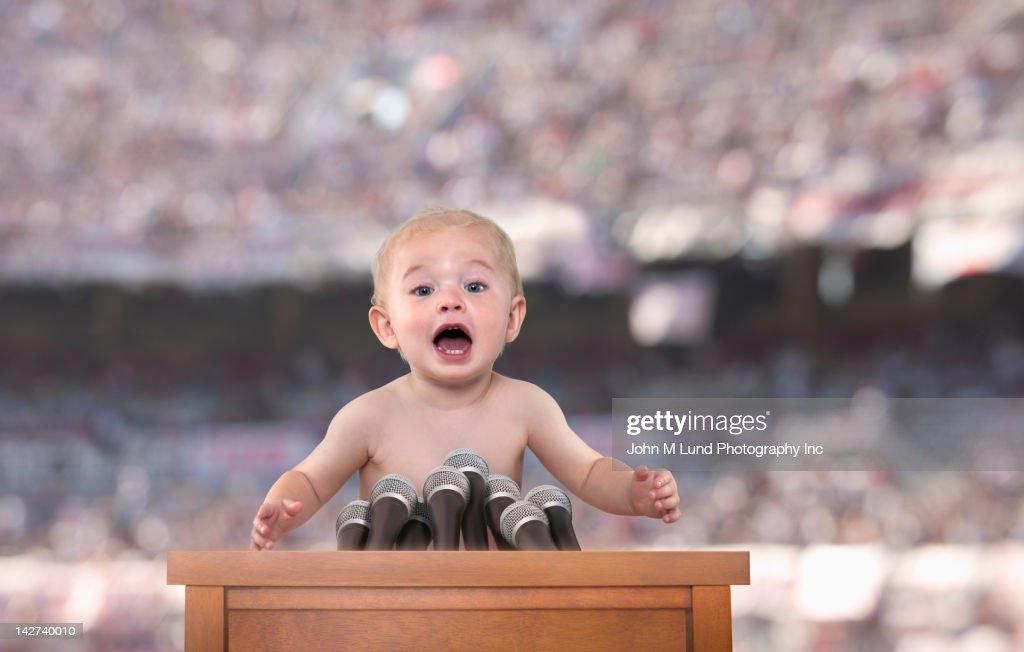 Caucasian baby speaking at podium : Foto de stock
