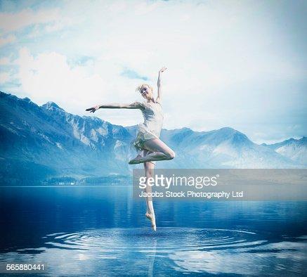 Caucasian ballerina balancing on lake surface
