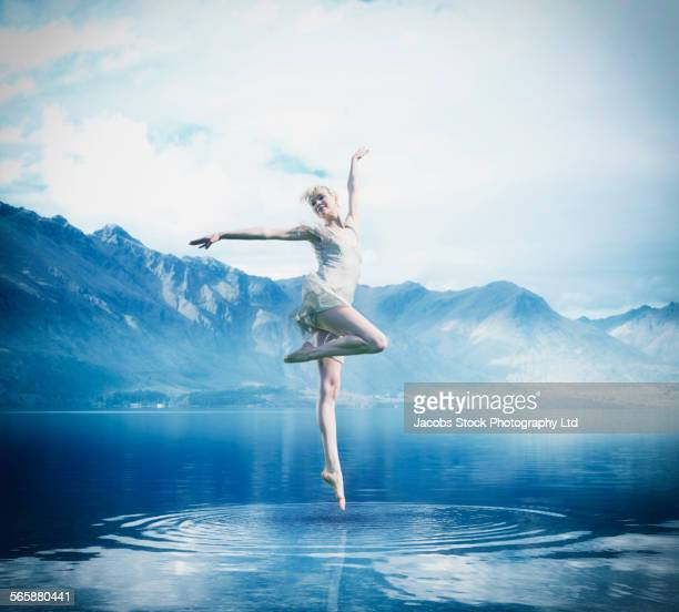 Caucasian ballerina balancing on lake surface
